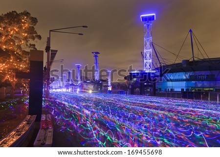 sydney electric run charity running festival after sunrise blurred river of racing athletes with neon glow sticks at olympic park - stock photo