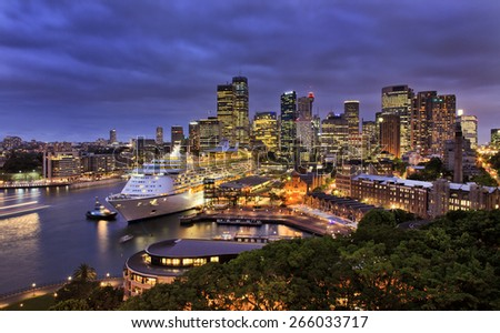 sydney harbour and city CBD at sunset with ocean liner at overseas terminal illuminated with lights
