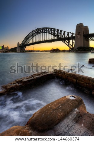 Sydney Harbour Bridge with rocks in the foreground  - stock photo
