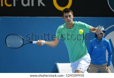 SYDNEY - JAN 9: Bernard Tomic from Australia hits for a forehand in his second round match in the APIA Sydney Tennis International. Sydney January 9, 2013. - stock photo