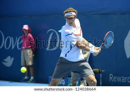 SYDNEY - JAN 9: Denis Istomin from Uzbekistan hits a backhand in his second round match in the APIA Sydney Tennis International. Sydney January 9, 2013. - stock photo