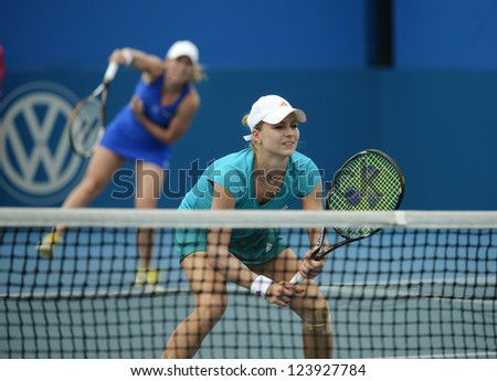 SYDNEY - JAN 8: Maria Kirilenko from the Russia at the net with doubles partner Lisa Raymond serving at the APIA Sydney Tennis International. Sydney January 8, 2013. - stock photo