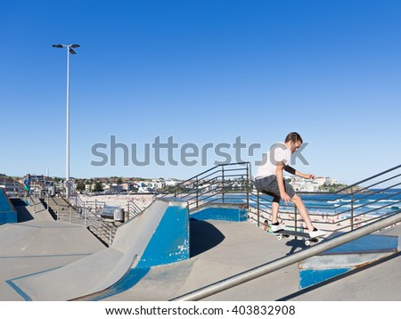 Sydney - March 1, 2016: skate boarder performs tricks in Sate Park with interesting slides at the beach and people sunbathing by the sea March 1, 2016, Sydney, Australia