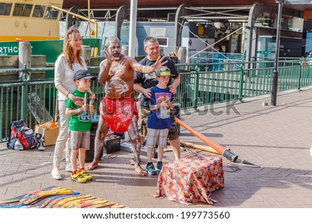 SYDNEY - MAY 10: Tourists take a photo with Aborigin who performed his music at Sydney harbour on May 10, 14 in Sydney. Aborigin is the original population of Australia. - stock photo