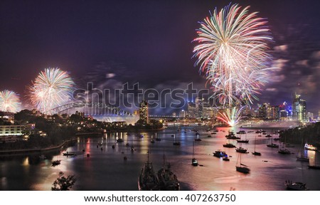 Sydney New Year eve fireworks over Harbour with bridge and city CBD buildings reflecting colourful fire balls in blurred water. - stock photo