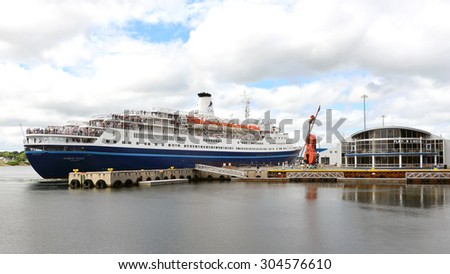 SYDNEY, NOVA SCOTIA, CANADA - AUG 8, 2015:  The MS Marco Polo pulling out of dock near the Joan Harris Cruise Pavilion, and the world's largest fiddle in Sydney, Cape Breton, Nova Scotia.   - stock photo