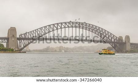 SYDNEY, NSW/AUSTRALIA - NOV 3, 2015: Ferry boat motors past the Sydney Harbour Bridge on a misty morning, in New South Wales, Australia. - stock photo