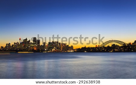 Sydney panoramic cityline from CBD to Harbour Bridge at sunset from Cremorne point over blurred calm harbour waters with illuminated buildings and landmarks - stock photo