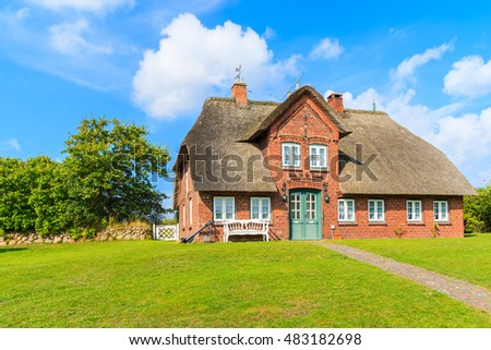 SYLT ISLAND, GERMANY - SEP 6, 2016: typical red brick Frisian house with thatched roof on Sylt island in List village, Germany.