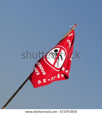 Symbol forbidden to swim - warning of danger at sea - flag - isolated - blue sky background