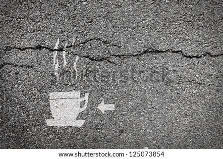 Symbol of a cup of steaming hot coffee with an arrow painted on the surface of a cracking asphalt road for the concept of highway rest stop cafe. - stock photo