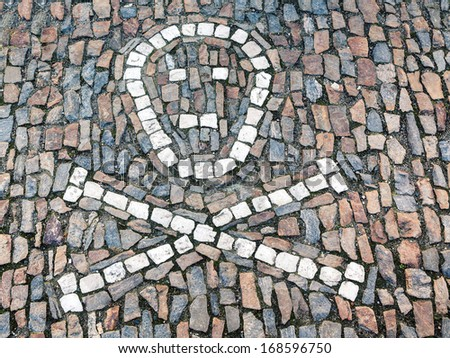 Symbol of a human skull with two crossed femur bones on the sidewalk,  built with stone mosaic - stock photo
