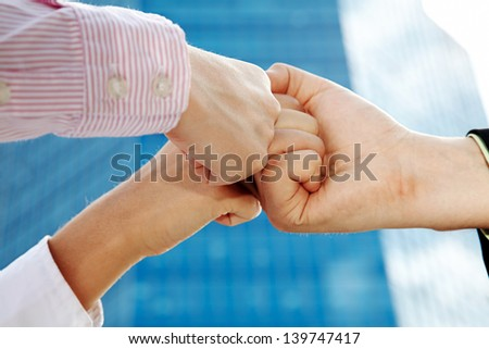 Symbol of business team: human fists making union
