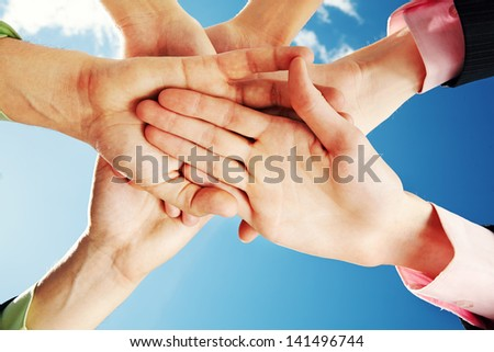 Symbol of business team: pile of people hands making union over blue sky - stock photo