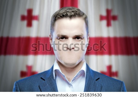Symbol of censorship and freedom of speech: a young man without a mouth on a background of the national flag of Georgia - stock photo