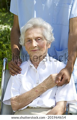 Symbol of comfort and support from care giver to smiling elderly woman outdoor - stock photo
