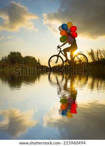Symbol of easy birthday celebration peace tranquility Young Girl in dress with sunglasses riding bicycle flying air balloons on leash yellow sun set ray sky background No face Unrecognizable person - stock photo