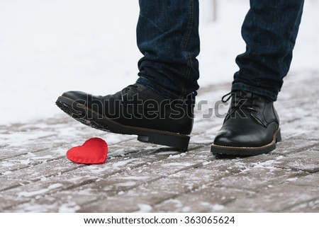 Symbol of end of love. Man treads decorative red heart - stock photo