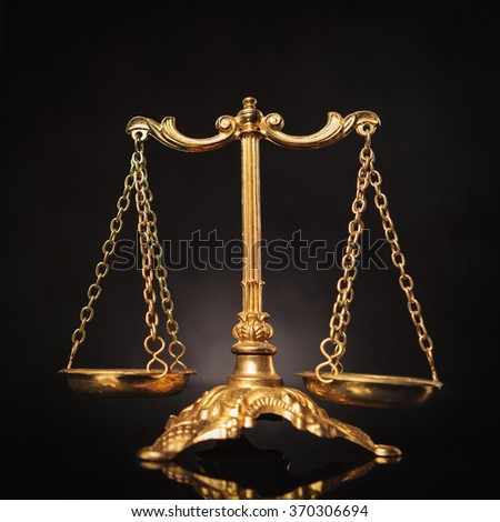 Symbol of justice, golden law scales on dark studio background - stock photo