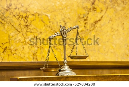 Symbol of law and justice in the empty courtroom, law and justice concept, focus on the scales