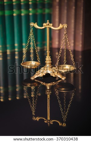 Symbol of law and justice, law and justice concept, golden scales in front of a row of books  - stock photo
