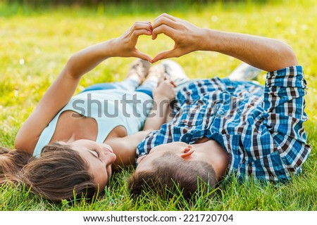 Symbol of love. Couple making heart shape with hands, lying on the grass - stock photo