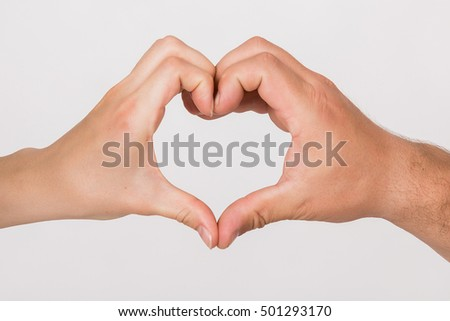 Symbol of love - Young dates hands making heart in isolation.