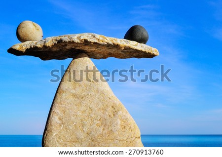Symbol of scales is made of pebbles at the sea  - stock photo