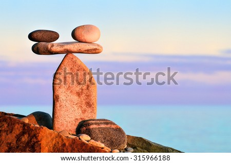 Symbol of scales is made of pebbles on the stony seashore - stock photo