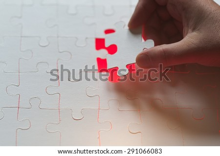 Symbol of solutions of business concepts, hand sets last puzzle piece a with red glowing background.
