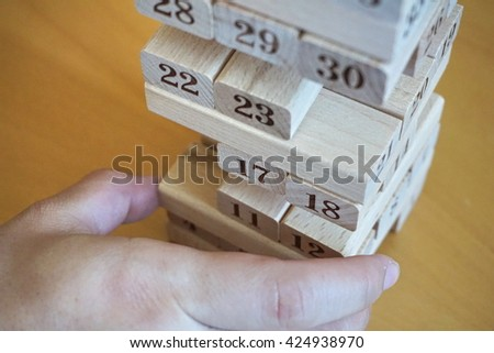 Symbol of stability and stabilization in a form of wooden bricks piled up in a stack in a kids game (jenga) where children build a vertical tower - stock photo