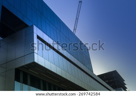 Symbol of success, Late evening light falling on glass window of new modern building under construction - stock photo
