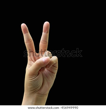 Symbol of victory, Woman hand making sign on black background.