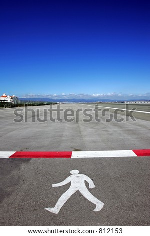 Symbol of walking man on runway at Gibraltar airport with deep, rich blue sky on a sunny day. - stock photo