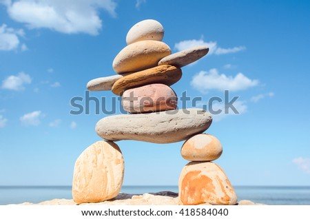 Symbolic figurine of inukshuk of the pebbles on sky background - stock photo