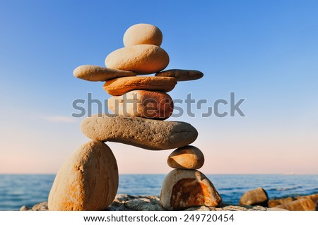Symbolic figurine of inukshuk of the pebbles on the coast - stock photo