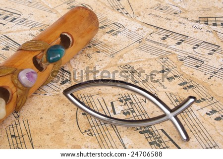 Symbolic fish and flute on a music sheet - stock photo
