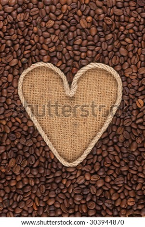 Symbolic heart made of rope lies on sackcloth and coffee beans, with space for your text