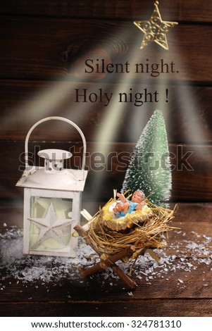symbolic nativity scene with baby Jesus figurine lying on a hay in the manger and star with light rays and christmas carol text on wooden background - stock photo