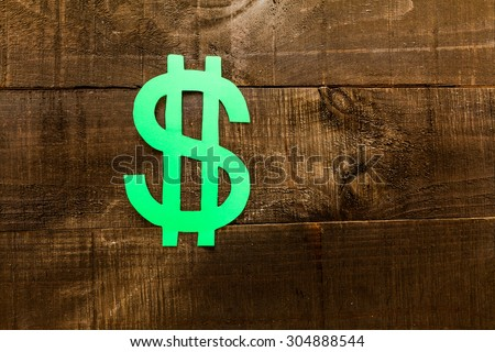 Symbols of dollar on dark wooden background