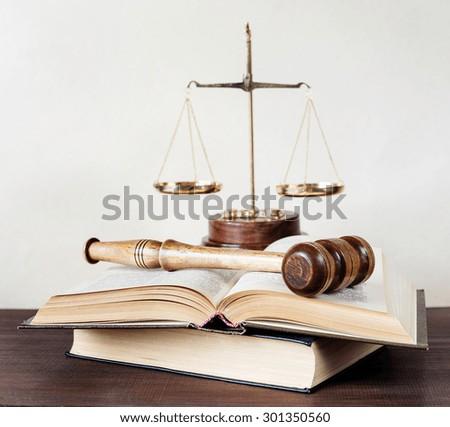 Symbols of law: wood gavel, soundblock, scales and opened volumetric old books - stock photo