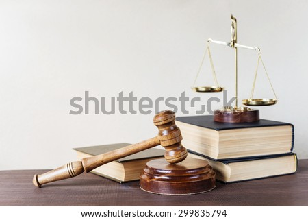 Symbols of law: wood gavel, soundblock, scales and three thick old books - stock photo
