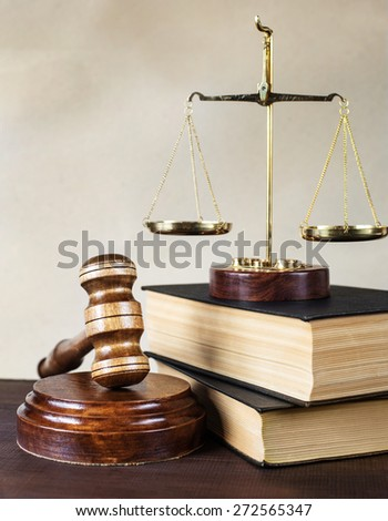 Symbols of law: wood gavel, soundblock, scales and two thick old books