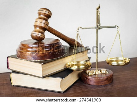 Symbols of law: wood gavel, soundblock, scales and two thick old books - stock photo