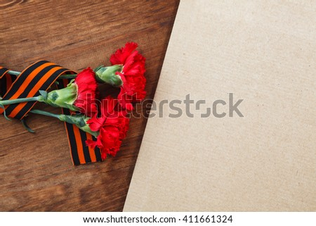 Symbols of Victory in Great Patriotic War three red flower and paper on a table.  selective focus image - stock photo
