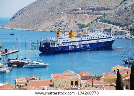 SYMI, GREECE - JUNE 18, 2011: Blue Star Ferries ship Diagoras docks at Yialos harbour on the Greek island of Symi. The 141mtr ship was built in 1990. - stock photo
