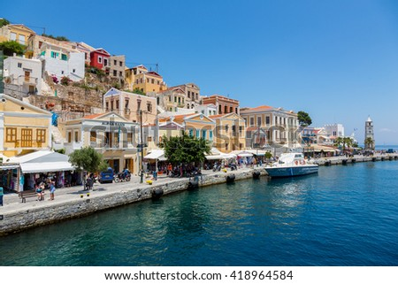 SYMI, GREECE - JUNE 12, 2015: The main street along the coast in Yialos harbour on June 12, 2015 on Symi island, Greece. Symi is easy and most popular destination for day tripping from Rhodes island. - stock photo