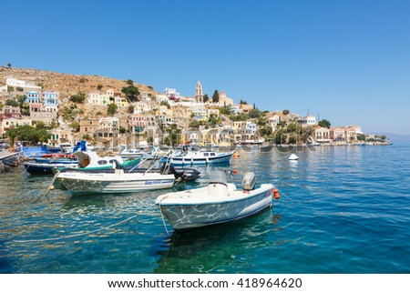 SYMI, GREECE - September 6,2015: Fishing boats moored in Yialos harbour and a beautiful view on a color houses. Symi is easy and most popular destination for day tripping from Rhodes island.