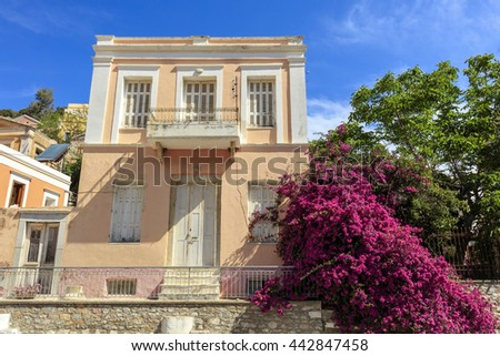 SYMI ISLAND, GREECE - JUNE 11, 2016: Old two storey house with pink bougainvillea  on the Greek island of Symi. - stock photo