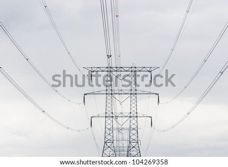 symmetric power lines against a cloudy sky - stock photo
